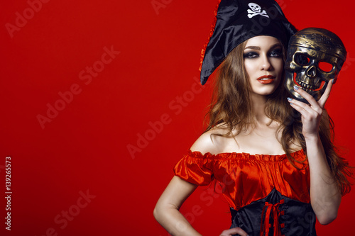 Valokuva  Portrait of gorgeous sexy woman with provocative make-up in pirate costume holding skull mask next to her face