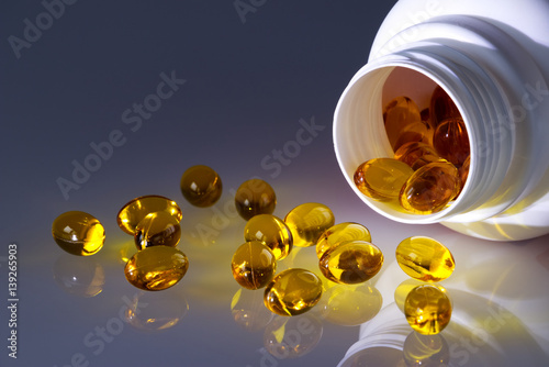 Valokuva  Omega 3 fish oil capsules spilled from a plastic bottle on a gradient background