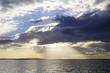 Bellissimo cielo nuvoloso con i raggi del sole che lo attraversano e si riflettono sulla superficie del mare
