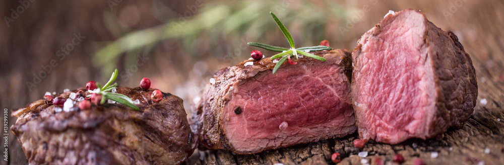Fototapety, obrazy: Grilled beef steak with rosemary, salt and pepper on old cutting board. Beef tenderloin steak.