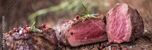 Grilled beef steak with rosemary, salt and pepper on old cutting board. Beef tenderloin steak.