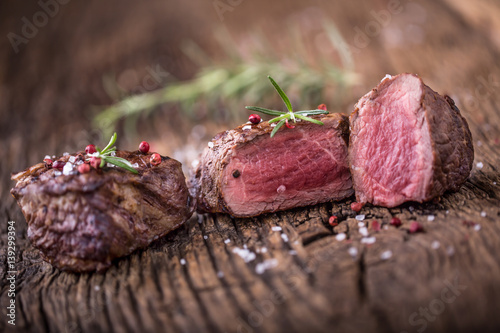 Fotografie, Obraz  Grilled beef steak with rosemary, salt and pepper on old cutting board