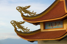 Two Fantastic Roosters On A Roof Of The Buddhist Temple Against The Background Of The Cloudy Sky. Phan Thiet, Vietnam