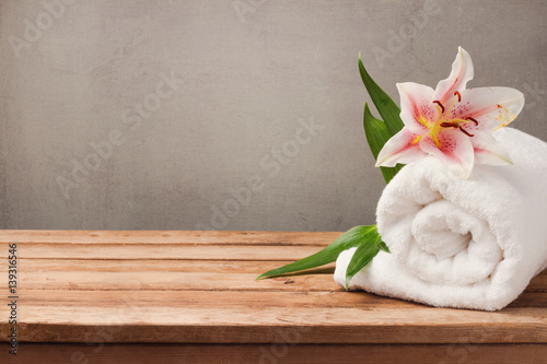 Türaufkleber Spa Spa and wellness concept with white towel and flower on wooden table over rustic background
