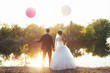 canvas print picture - Sunset. Newlyweds standing on the bank of the river holding hands. Balloons at the bride and groom.