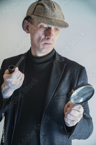 sherlock holmes in studio detective at work with magnifying glass and pipe Canvas Print