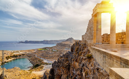Photo Stands Athens Greece. Rhodes. Acropolis of Lindos. Doric columns of the ancient Temple of Athena Lindia setting sun above the columns