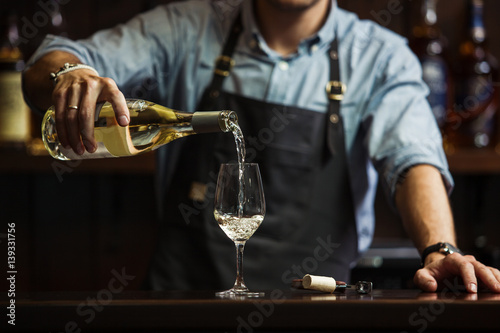 Fotografia  Male sommelier pouring white wine into long-stemmed wineglasses.