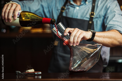 Fotografía  Sommelier pouring red wine into carafe to make perfect color