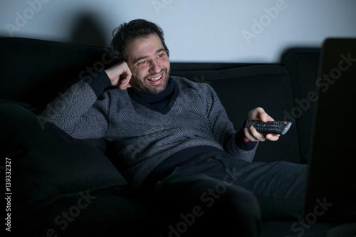 Photo  Smiling man watching television at night