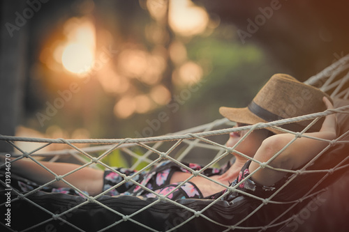 beautiful young woman lying in a hammock and relaxing with hat on her head
