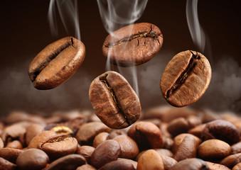 Fototapeta Closeup falling coffee bean with smoke on brown background