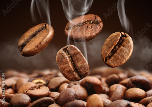 Poster Café en grains Closeup falling coffee bean with smoke on brown background