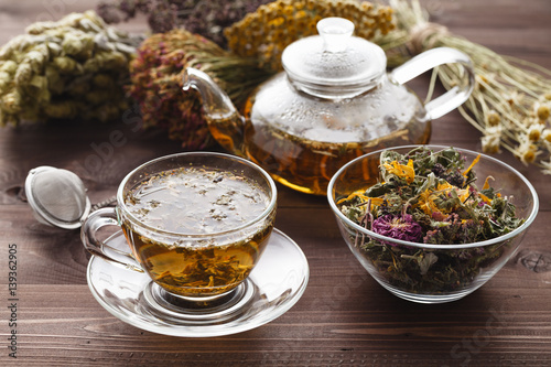 medicinal tea in glass cup with dried herb in bowl Wallpaper Mural