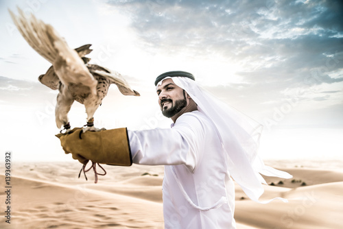 Recess Fitting Dubai Arabic man with traditional emirates clothes walking in the desert with his falcon bird