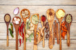 Various of spices and herbs in wooden spoons. Flat lay of spices ingredients chilli ,pepper corn, garlic, thyme, oregano, cinnamon, star anise, nutmeg, mace, sage and parsley on the wooden background.