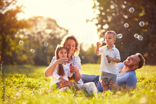 Fotografie, Obraz  Family with children blow soap bubbles outdoor