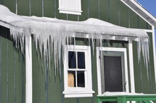 Icicles In Front Of A Green House