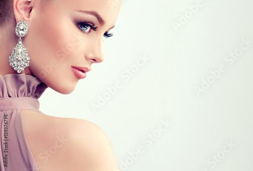 fototapeta na szkło Beautiful girl with evening makeup and large earrings jewelry .