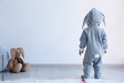 Cute little child in bunny costume standing at home