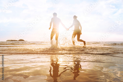 Photo  happy young couple having fun on the beach at sunset, water splash, enjoying lif