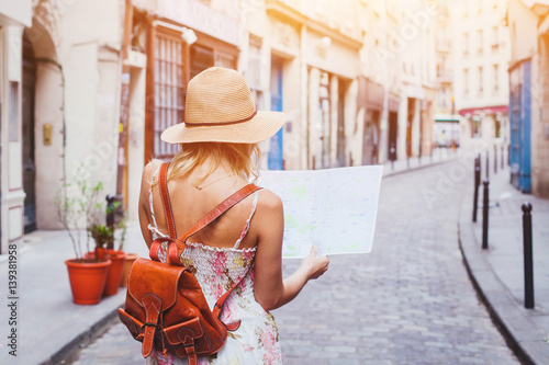 Fotografia  woman tourist looking at the map on the street of european city, travel to Europ