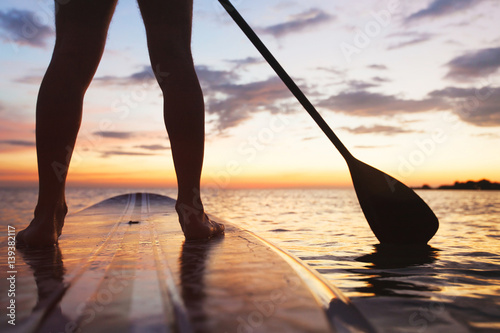 Fotografia, Obraz  paddle board on the beach, close up of standing  legs and paddle