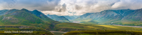 Panoramic landscape of Denali National Park with grass,clouds and sunlight