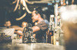 canvas print picture - Blurred defocused side view of barman and people drinking and having fun at cocktail bar - Social gathering concept with people enjoying time together - Warm retro contrast filter with focus on shaker