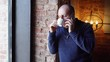 Man standing near a window in a cafe and drink coffee or tea, breakfast in restaurant. Talking on the phone.