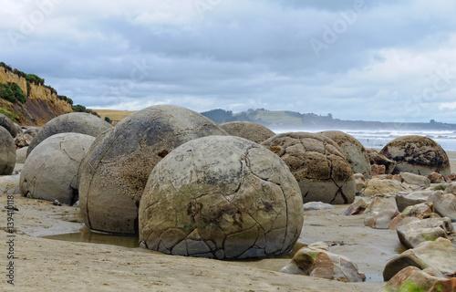 Photo  Moeraki Boulders are large, spherical boulders lying on the Koekohe Beach at Moe
