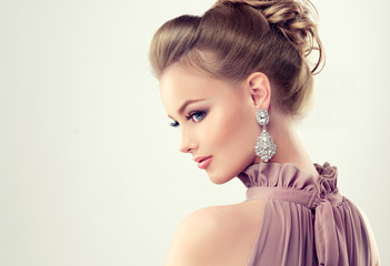 Beautiful girl with elegant hairstyle and big earrings jewelry .