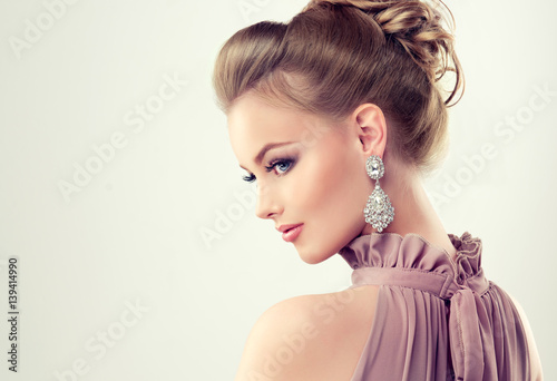 Beautiful girl with elegant hairstyle and big earrings jewelry Fototapet