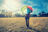 Fototapeta Tęcza - woman holding rainbow umbrella and watching sunset in the nature, birds flying above ,spring background