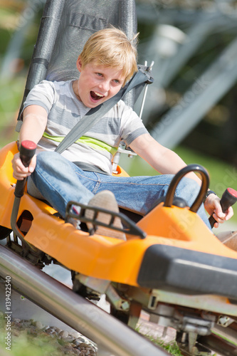 Happy Boy Riding at Bobsled Roller Coaster Rail Track in Summer Amusement Park