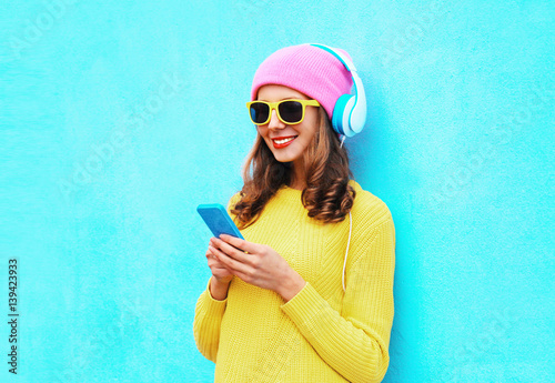 Fashion prettyt carefree woman listening music in headphones browsing smartphone wearing a colorful pink hat yellow sunglasses sweater over blue background - 139423933