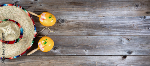 Obraz Traditional maracas and large sombrero for Cinco de Mayo holiday party celebration on rustic wooden boards - fototapety do salonu