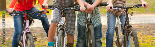 Teenage boys and girl riding bicycles in the nature on sunny spring day Canvas Print