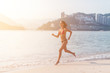 Fit female athlete wearing bikini running on beach with sun shining in camera and hotel resort hills in background