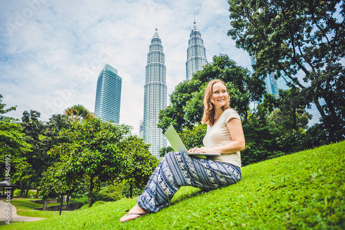 Foto op Aluminium Kuala Lumpur A young woman in casual dress using laptop in a tropical park on the background of skyscrapers. Mobile Office concept