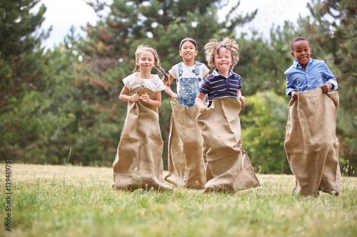 Foto Gruppe Kinder beim Sackhüpfen