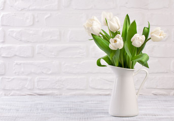 Fresh white tulip flowers bouquet in front of white brick wall.