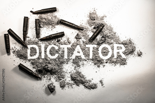 Fotografie, Obraz  Dictator word written in  ash, dirt, dust with bullets around as dictatorship, p