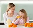 Mother and daughter make orange juice on a juicer