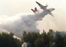 Plane Drops Fire Retardant And Water On A Forest Fire