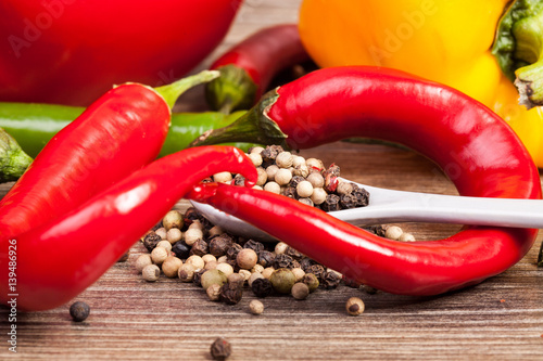 Staande foto Hot chili peppers Spicy and sweet pepper on wooden background