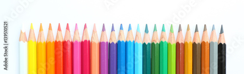 Photo colored pencils row with wave on white background