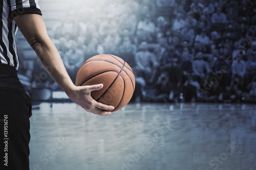 basketball referee holding a basketball at a game in a crowded sports arena. Holding the ball in his hand during a timeout. Selective focus on the ball. The fans and crowd and basketball court