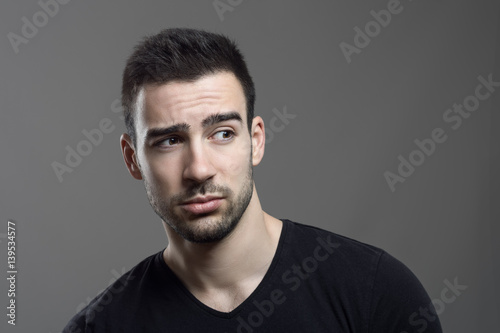 Fototapety, obrazy: Moody portrait of confused man facial reaction looking away over dark gray studio background.