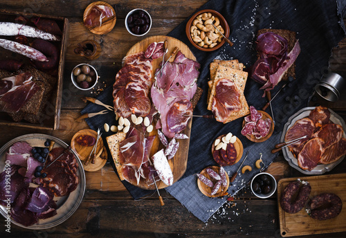 Foto op Aluminium Buffet, Bar Tapas selection. A cutting board with charcuterie. Spanish cured meat, jamon, lomo, chorizo, salchichon. Charcuterie concept. Top view.